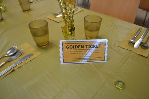 A photograph of a set golden table with the golden ticket on top.