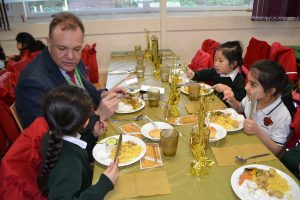 A headteacher enjoying lunch with students at a golden ticket table,