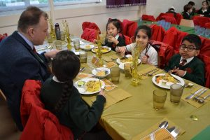 Winners of the golden ticket sat at the golden table with the headteacher.