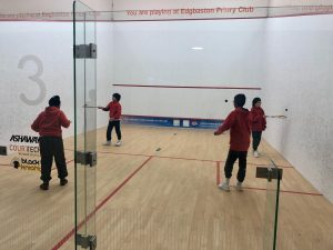 A group of students playing squash.