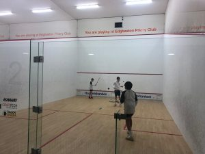 a pair of students playing squash