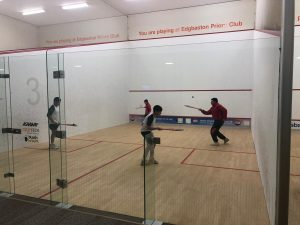 Three children playing squash