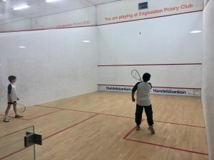 a pair of students taking turns playing squash