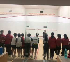 Children lined up at a squash court