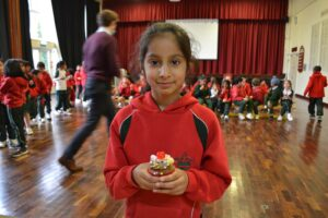 Image of a Hallfield pupil holding a decorated Easter cupcake.
