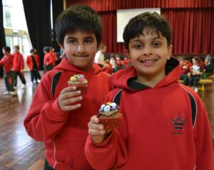 Image of Hallfield pupils holding their decorated Easter cupcakes.