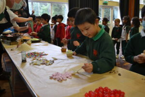 Image of Hallfield pupils decorating Easter cupcakes.