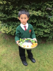 Image of a Hallfield pupil holding a tray of food for the Guinea pigs.
