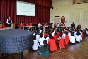 Image of Hallfield pupils sitting in the hall taking part in the Inter-House quiz.