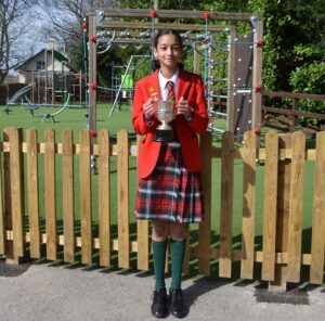 Image of Hallfield pupil holding the Easter Greenwood Cup award.
